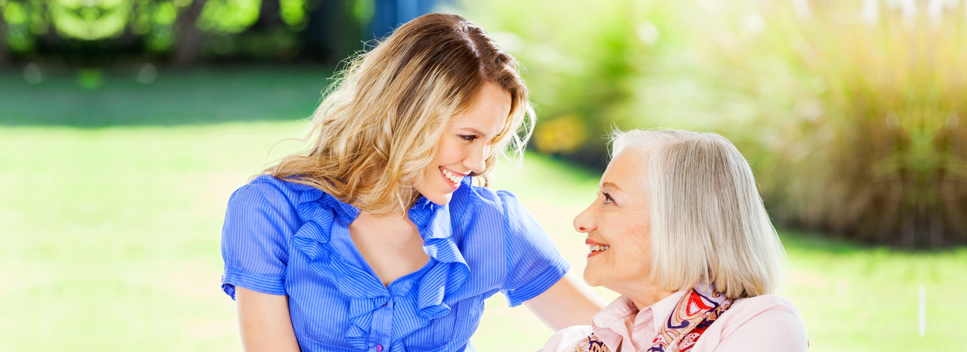 a lady and an old woman smiling at each other
