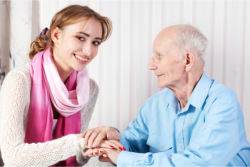 a lady holding an old man's hand