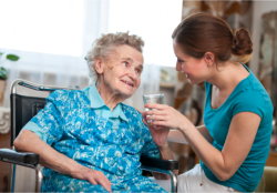a lady assisting an old woman to drink medicines
